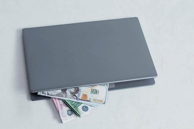 Concept de travail et d'investissement en ligne. ordinateur portable avec un paquet de billets en dollars et en euros sur un fond blanc.