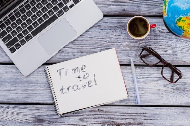 Concept de travail et de vacances. le temps de voyager. accessoires d'employé de bureau sur une table en bois blanc. vue de dessus à plat.
