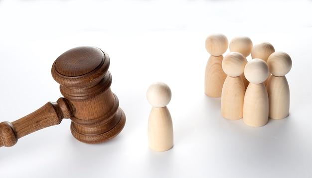 Concept de tribunal et de droit. beaucoup de personnages en bois et marteau de juge.
