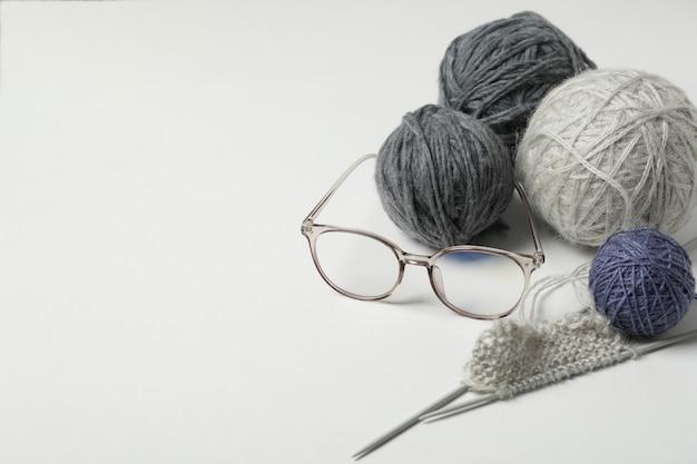 Concept de tricot avec des pelotes de laine sur fond clair.