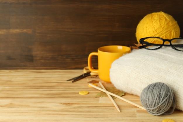 Concept de tricot avec des pelotes de laine sur table en bois.