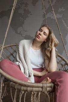 Concept de tristesse et de réflexion, belle jeune fille sur la balançoire dans une chambre confortable