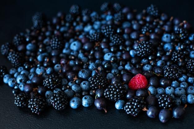 Concept d'unicité. pas comme les autres. framboise rouge dans un mélange en tas de baies noires de cassis et de myrtille