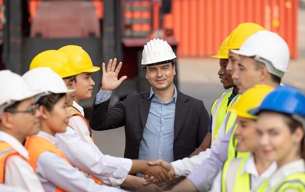 Concept d'unité et de succès vue de dessous des gens de l'équipe d'ingénieur debout mains tenant ensemble au chantier de conteneurs.