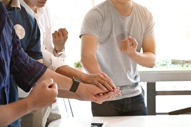 Concept d'unité et de travail d'équipe; photo recadrée de gens d'affaires en démarrage rassemblant leurs mains. pile de mains