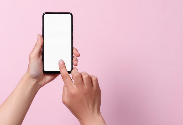 Concept d'utilisation du smartphone. un smartphone avec un écran blanc blanc dans les mains d'une femme.