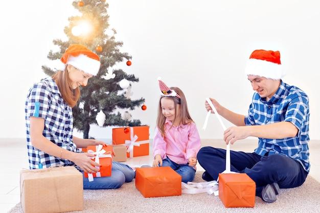 Concept de vacances et de cadeaux - portrait d'une famille heureuse ouvrant des cadeaux au moment de noël.