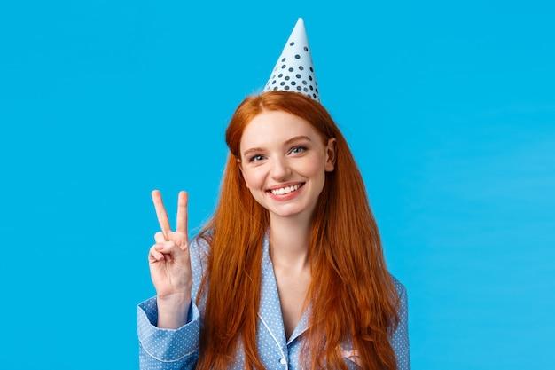 Concept de vacances, de célébration et de félicitations. rousse joyeuse femme européenne avec b-day hat montrant signe de paix, portant des vêtements de nuit, fête d'anniversaire, souriant sur fond bleu