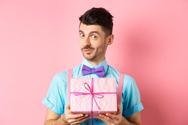 Concept de vacances et de célébration. funny guy avec moustache montrant jolie boîte-cadeau enveloppée dans du papier de fête, regardant la caméra, vous présentant, debout sur fond rose.