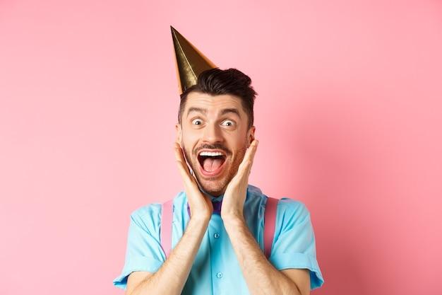 Concept de vacances et de célébration. gros plan d'un mec drôle au chapeau d'anniversaire criant surpris, criant de joie, recevant un cadeau génial, debout heureux sur fond rose.