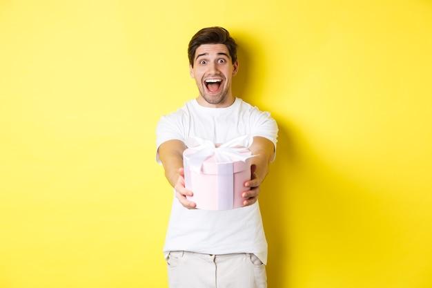 Concept de vacances et de célébration. heureux homme souhaitant une bonne année, vous donnant un cadeau, debout sur fond jaune.