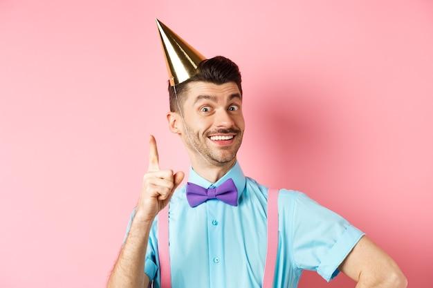 Concept de vacances et de célébration. image d'un homme heureux en chapeau de fête d'anniversaire présentant une idée, levant le doigt et souriant, ayant un plan ou une solution, debout sur fond rose.