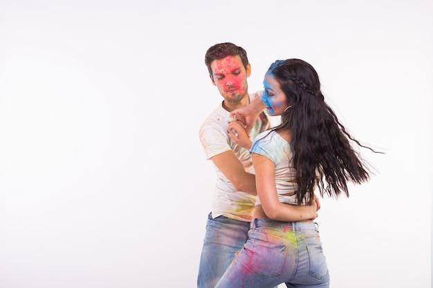 Concept de vacances, de danse sociale, de holi et de personnes - heureux couple s'amusant couvert de peinture et de danse bachata ou kizomba sur un mur blanc avec espace de copie
