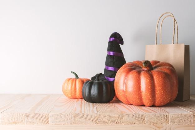 Concept de vacances avec décor de citrouille d'halloween et sac en papier cadeau sur table en bois.