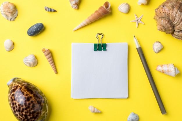 Le concept de vacances d'été. bloc-notes espace pour le texte. coquilles de mer sur fond jaune