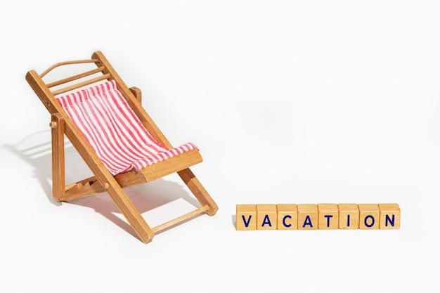 Concept de vacances d'été. chaise et blocs de bois avec texte vacances isolé sur fond blanc.