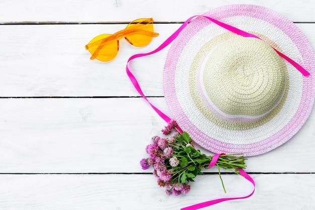 Le concept des vacances d'été. un chapeau, des lunettes de soleil et un bouquet de fleurs.