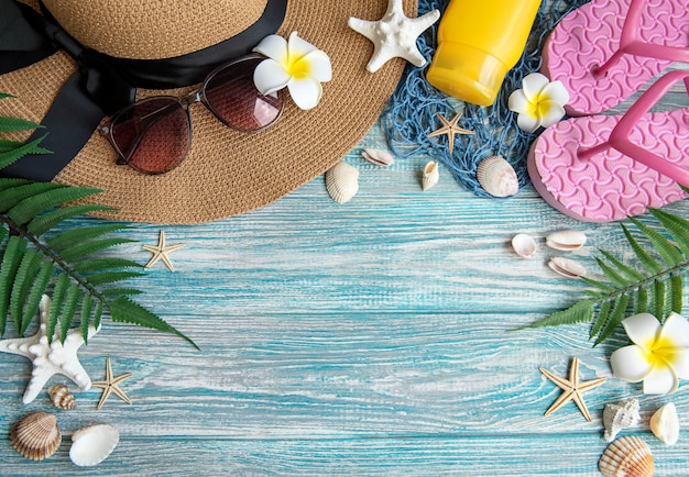 Concept de vacances d'été. chapeau de paille et accessoires de plage avec coquillages et étoiles de mer sur fond de bois bleu