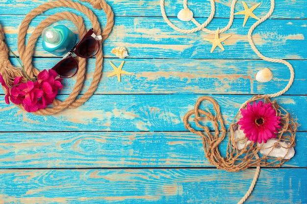 Concept de vacances d'été de cordes, lunettes de soleil et fleurs roses sur fond de bois bleu