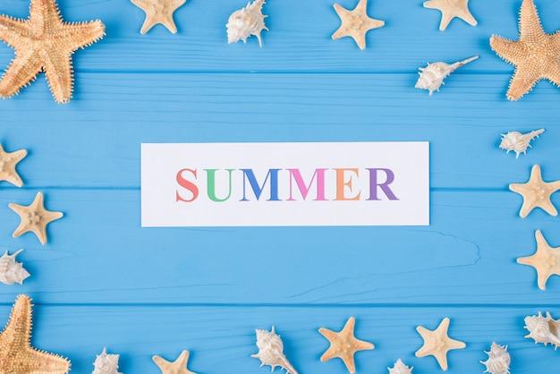 Concept de vacances d'été. haut au-dessus de la vue aérienne photo de mot été et coquillages et poissons de mer isolés sur fond de bois bleu