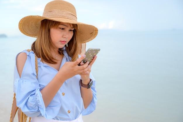 Concept de vacances d'été jeune femme vêtue d'une élégante robe bleue et chapeau de paille avec ciel bleu