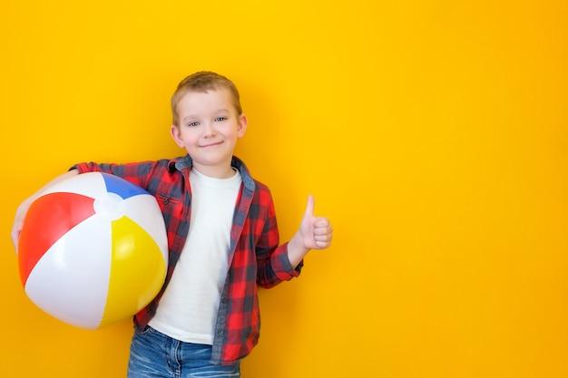 Concept de vacances d'été, portrait d'un petit enfant mignon et heureux, garçon souriant et tenant un ballon de plage, enfant s'amusant avec un ballon gonflable et montrant comme, tourné en studio isolé sur fond jaune