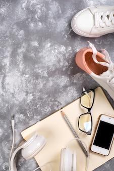 Concept de vacances d'été: smartphone, baskets blanches, bloc-notes, casque, stylo