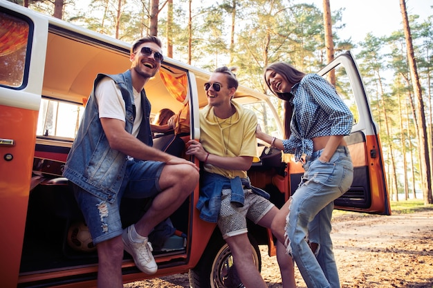 Concept de vacances d'été, voyage sur la route, vacances, voyage et personnes - souriant jeunes amis hippies s'amusant sur une voiture monospace.