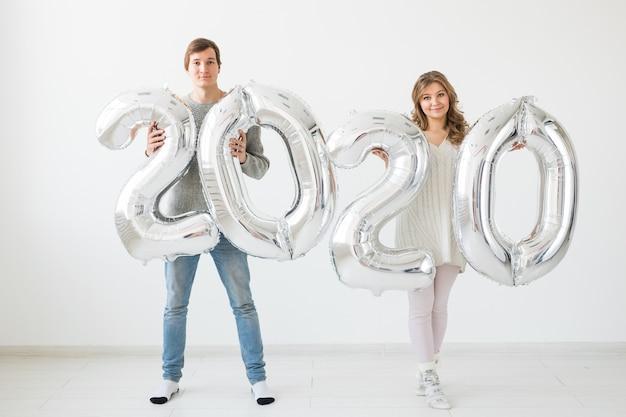 Concept de vacances, de fête et de fête - un couple d'amoureux heureux embrasse et détient des ballons d'argent 2020. célébration du nouvel an