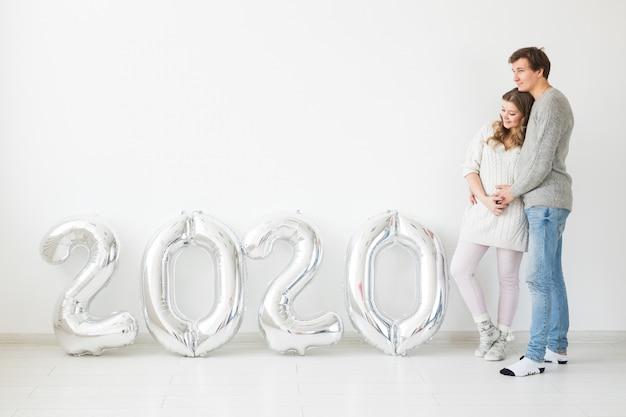 Concept de vacances, de fête et de fête - couple d'amoureux heureux près de ballons d'argent 2020. célébration du nouvel an