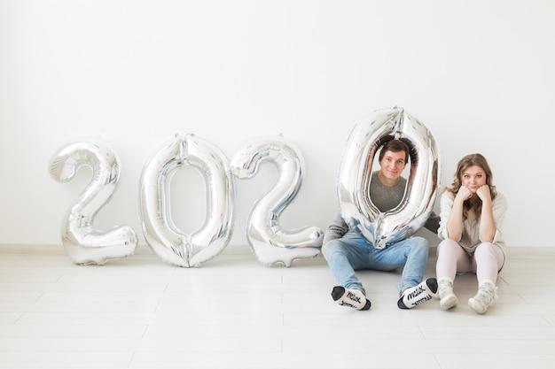 Concept de vacances, de fête et de fête - couple drôle assis sur un sol près de ballons d'argent 2020. célébration du nouvel an