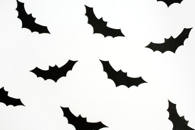 Concept de vacances d'halloween. chauves-souris en papier noir à la main sur blanc