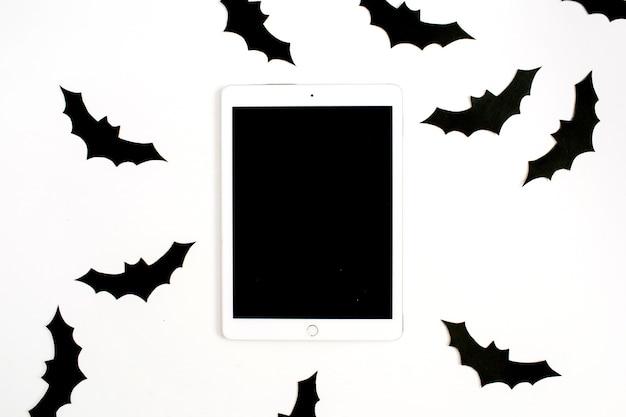 Concept de vacances d'halloween. tablette avec écran blanc et chauves-souris en papier noir à la main sur blanc