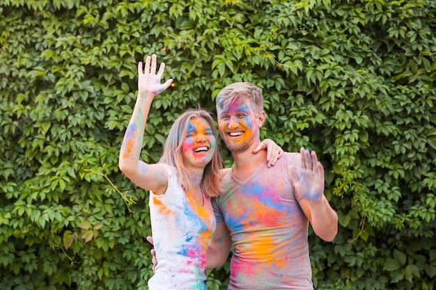 Concept de vacances, de holi et de personnes - couple heureux s'amusant recouvert de peinture.
