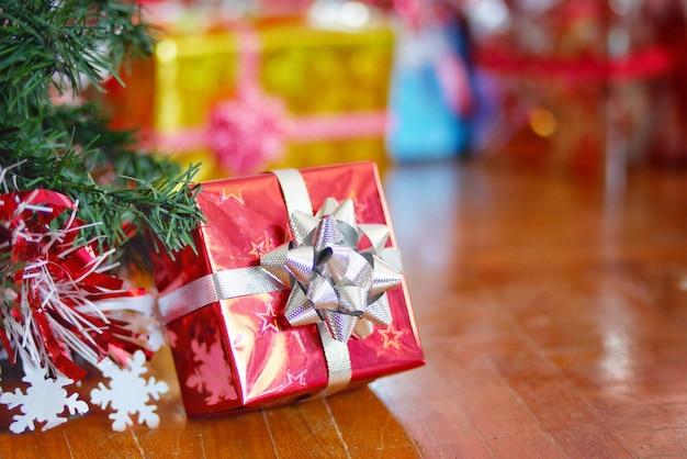 Concept de vacances de noël, une boîte cadeau rouge avec arbre de noël sur le plancher en bois.