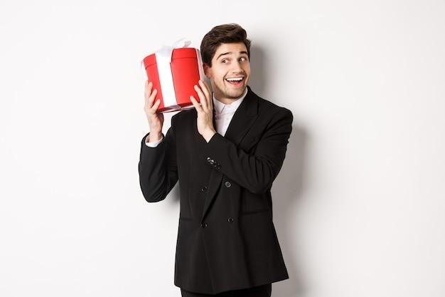 Concept de vacances de noël, de célébration et de style de vie. bel homme en costume noir, secouant une boîte avec un cadeau, se demandant ce qu'il y a à l'intérieur, debout sur fond blanc.