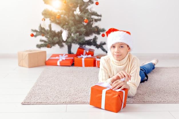 Concept de vacances, noël, enfance et personnes - un garçon adolescent souriant et heureux en bonnet de noel ouvre une boîte-cadeau sur fond d'arbre de noël.