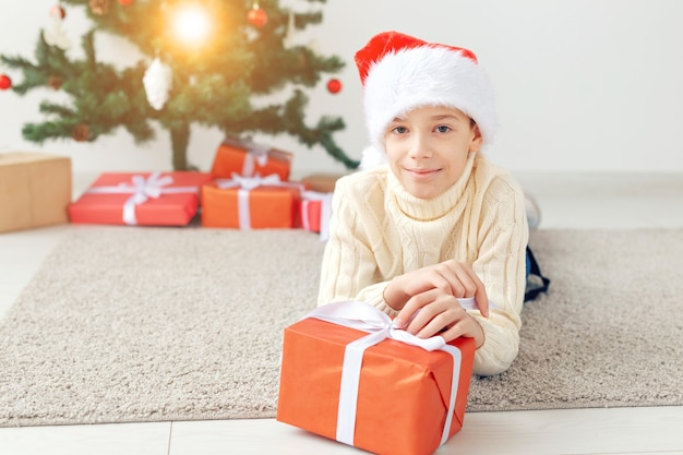 Concept De Vacances, Noël, Enfance Et Personnes - Un Garçon Adolescent Souriant Et Heureux En Bonnet De Noel Ouvre Une Boîte-cadeau Sur Fond D'arbre De Noël. Photo Premium