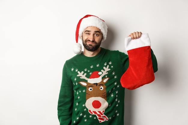 Concept de vacances de noël et d'hiver. mec mécontent déçu de cadeau en chaussette de noël, debout bouleversé en bonnet de noel sur fond blanc