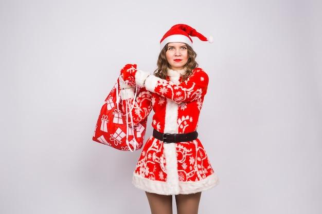 Concept de vacances, de noël et de personnes - femme en colère en costume de père noël avec sac de cadeaux.