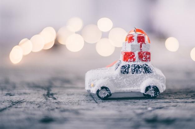 Concept de vacances de noël avec voiture de jouet et bokeh magique. espace de copie. fond abstrait