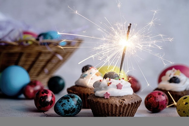 Concept de vacances de pâques. cupcake de pâques avec un sparkler décoré d'œufs de caille colorés