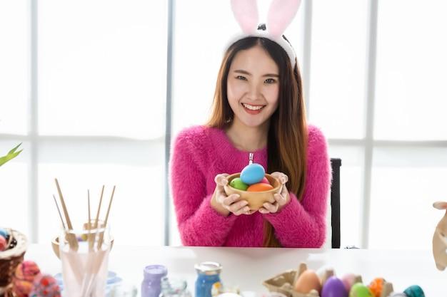 Concept de vacances de pâques, happy asian young woman show tenant un panier avec des oeufs de pâques colorés dans le fond de la salle blanche