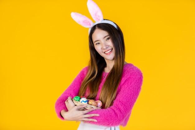 Concept de vacances de pâques, heureuse jeune femme asiatique portant des oreilles de lapin main tenant un panier avec des oeufs de pâques colorés en isolé sur fond de studio espace copie vierge jaune.