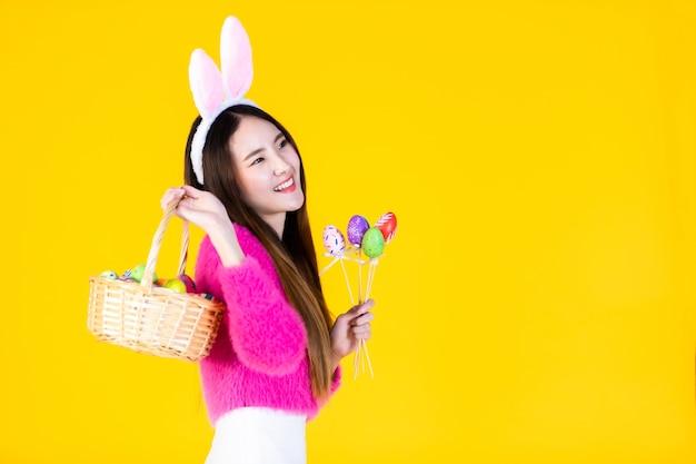 Concept de vacances de pâques, heureux jeune femme asiatique portant des oreilles de lapin main tenant un panier avec des oeufs de pâques colorés