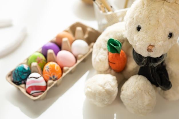 Concept de vacances de pâques, lapin tenant une poupée de carottes avec une boîte à œufs avec des œufs de pâques colorés sur fond de bois rustique de couleur pastel blanc avec espace.