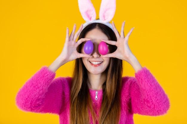 Concept de vacances de pâques, sourire heureux jeune femme asiatique portant des oreilles de lapin et brandissant un œuf de pâques coloré devant ses yeux brochettes isolées sur fond de studio espace copie vierge jaune.
