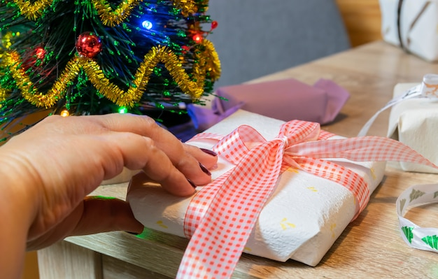 Concept de vacances et de personnes de noël: mains de femmes préparant des cadeaux de noël