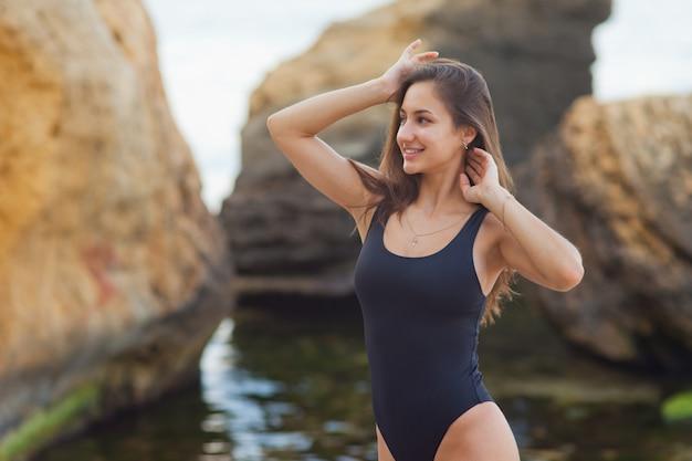 Concept de vacances sur la plage. repos d'été. jeune femme sexy en maillot de bain sur une plage sauvage avec des pierres