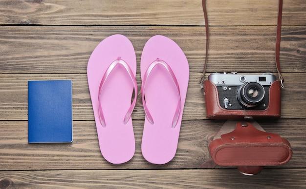 Concept de vacances sur la plage, tourisme. fond de voyageur d'été. tongs, appareil photo rétro, passeport sur fond de bois.
